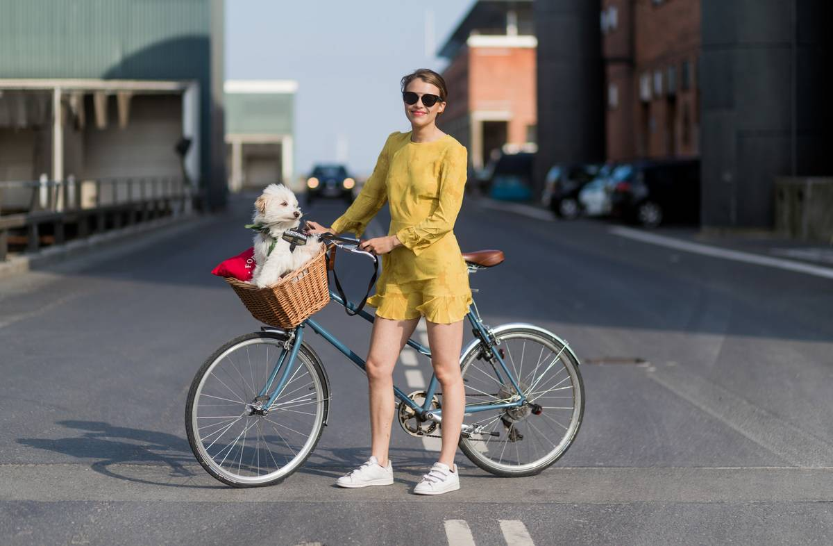 Woman poses with a bike with her dog wearing a yellow bow