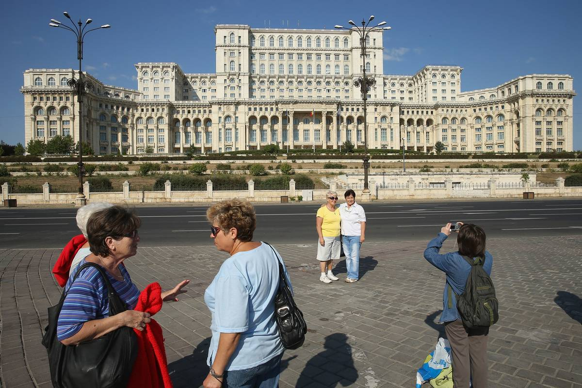 Tourists photograph one another in front of the Palace of the Parliament, built by former Romanian dictator Nicolae Ceausescu  in Bucharest, Romania