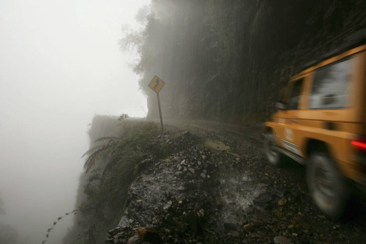 A car travels thin road on mountain side with nothing protecting from edge