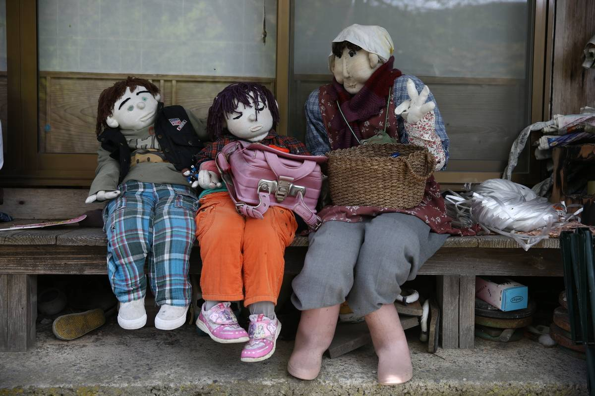 human sized dolls sitting on bench