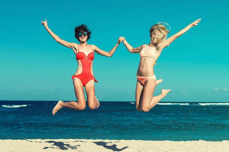 women holding hands and jumping on beach