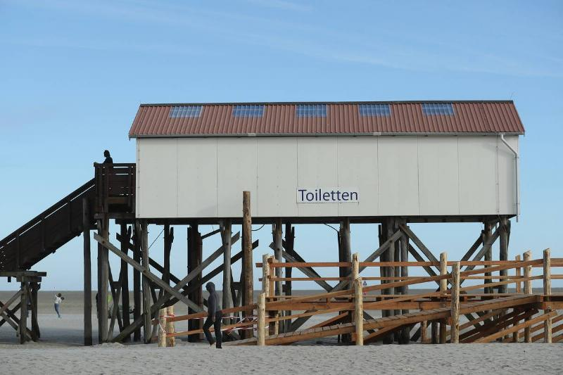A building housing public toilets stands on stilts at the beach