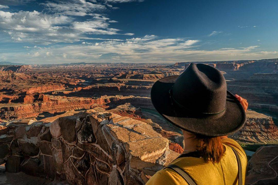 woman stares off cliff in black hat and yellow sweater