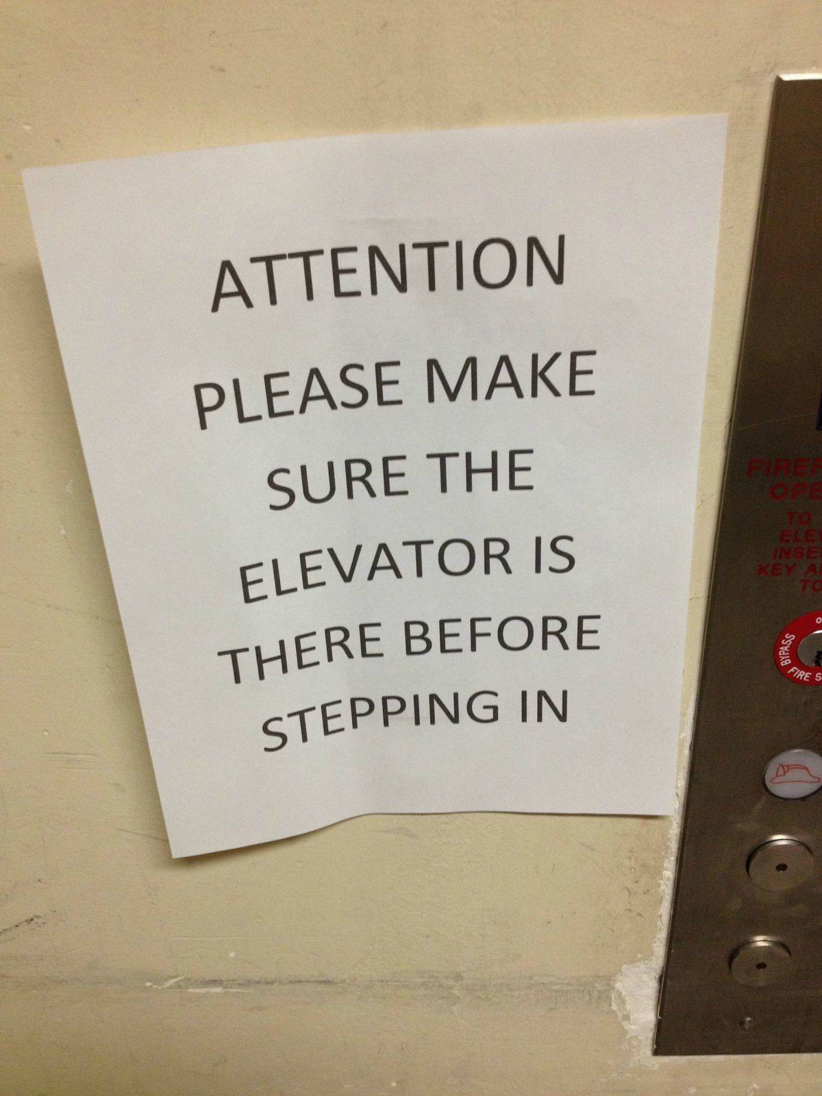 A sign warns people to make sure the elevator is there before stepping in.