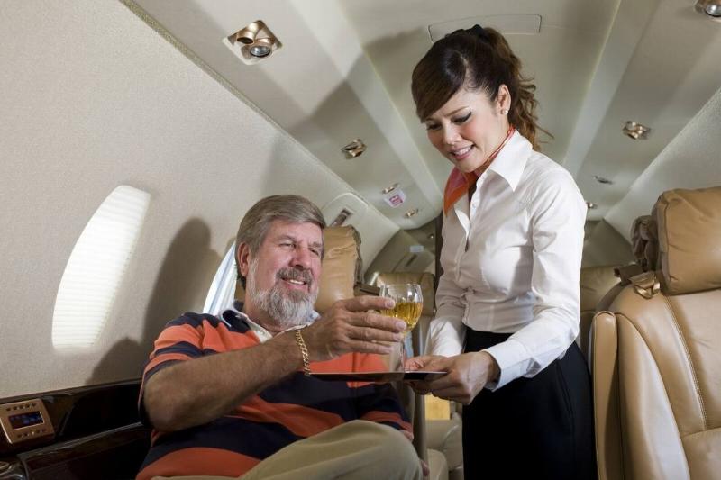 A passenger joyfully accepts a drink from a stewardess.