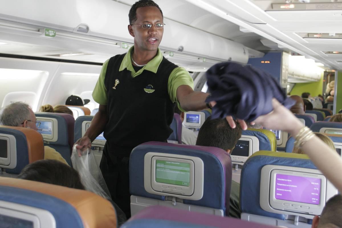 A flight attendant hands a blanket to a passenger.