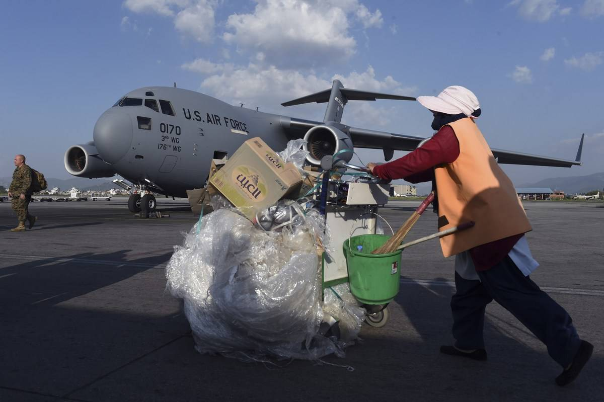 An employee takes out trash from an airplane.
