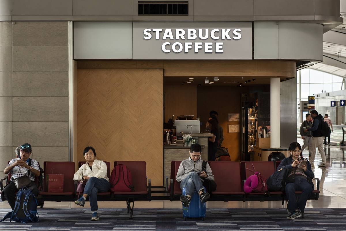 Passengers sit in front of a Starbucks Coffee in an airport.