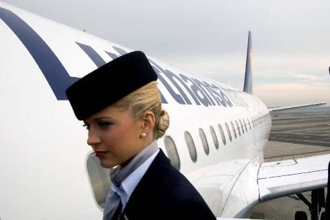 A stewardess is seen boarding a plane.