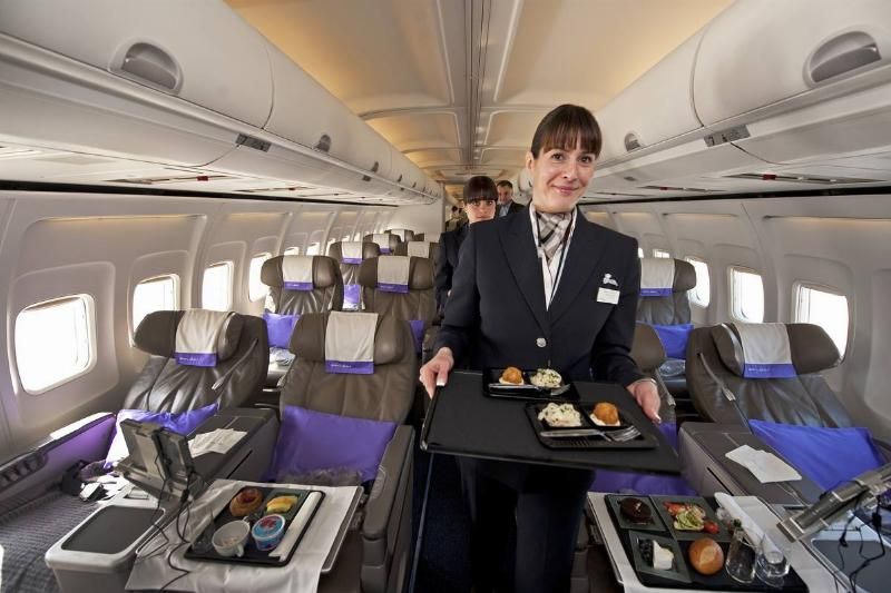 A flight attendant carries food down the aisle.