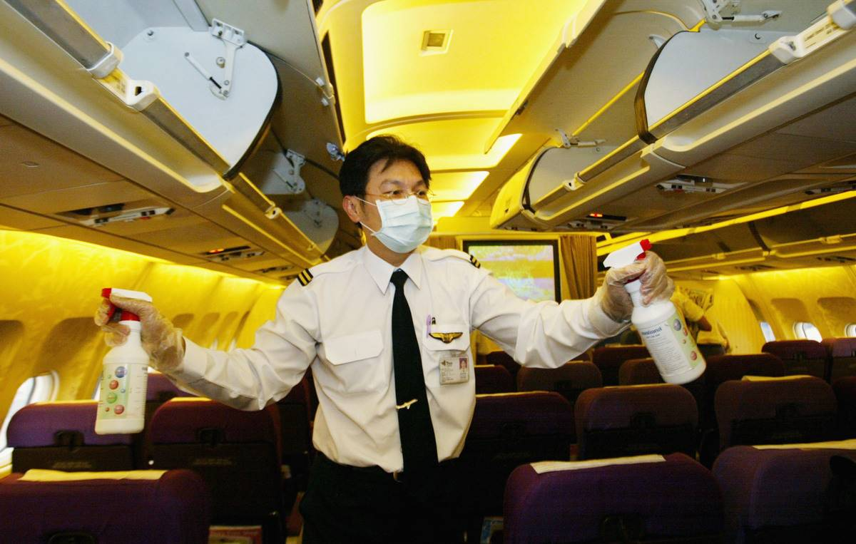 A flight attendant wears a mask as he disinfects the cabin with cleaning sprays.