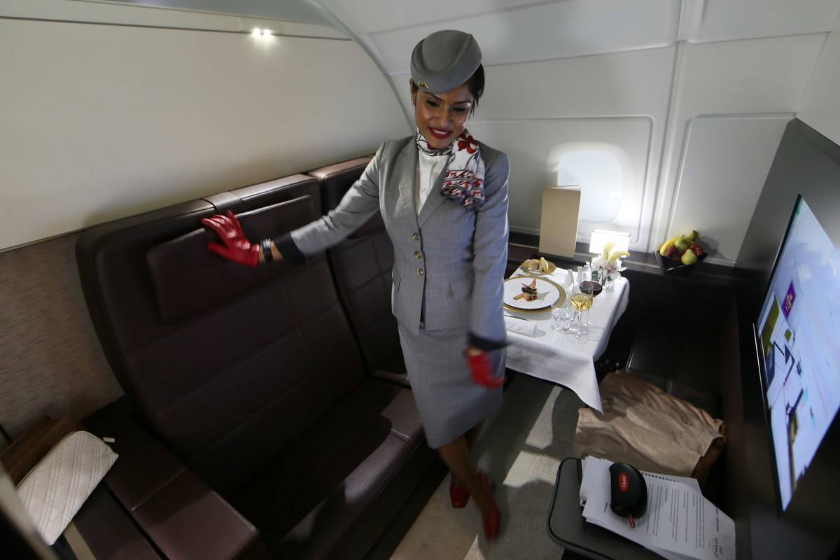 A stewardess stands in the first class suite.