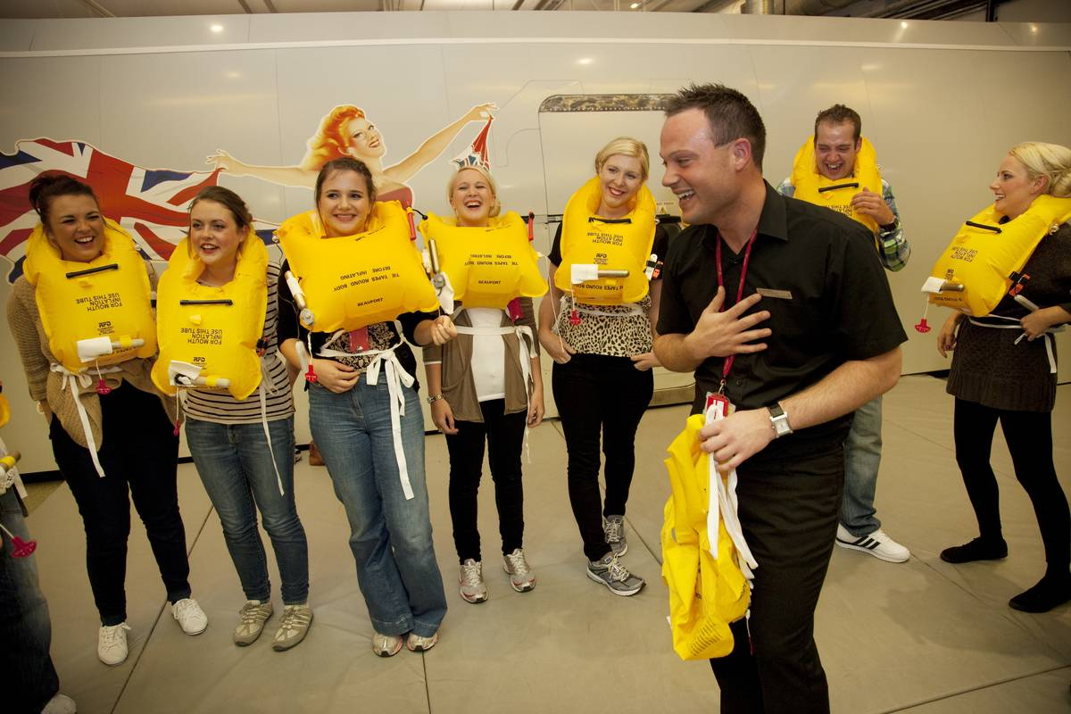 An instructor shows students how to put on life jackets in a flight attendant class.