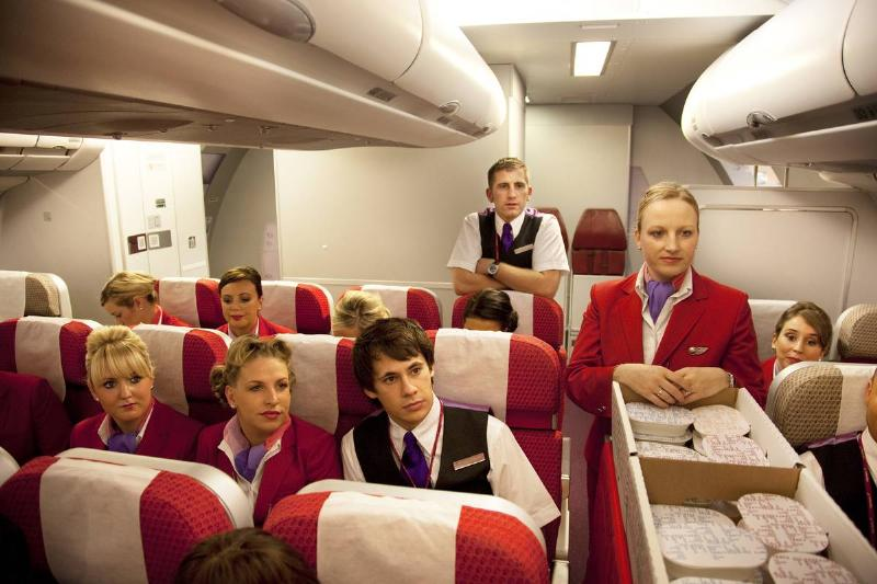 Flight attendants sit on a plane and listen to an instructor during classes.