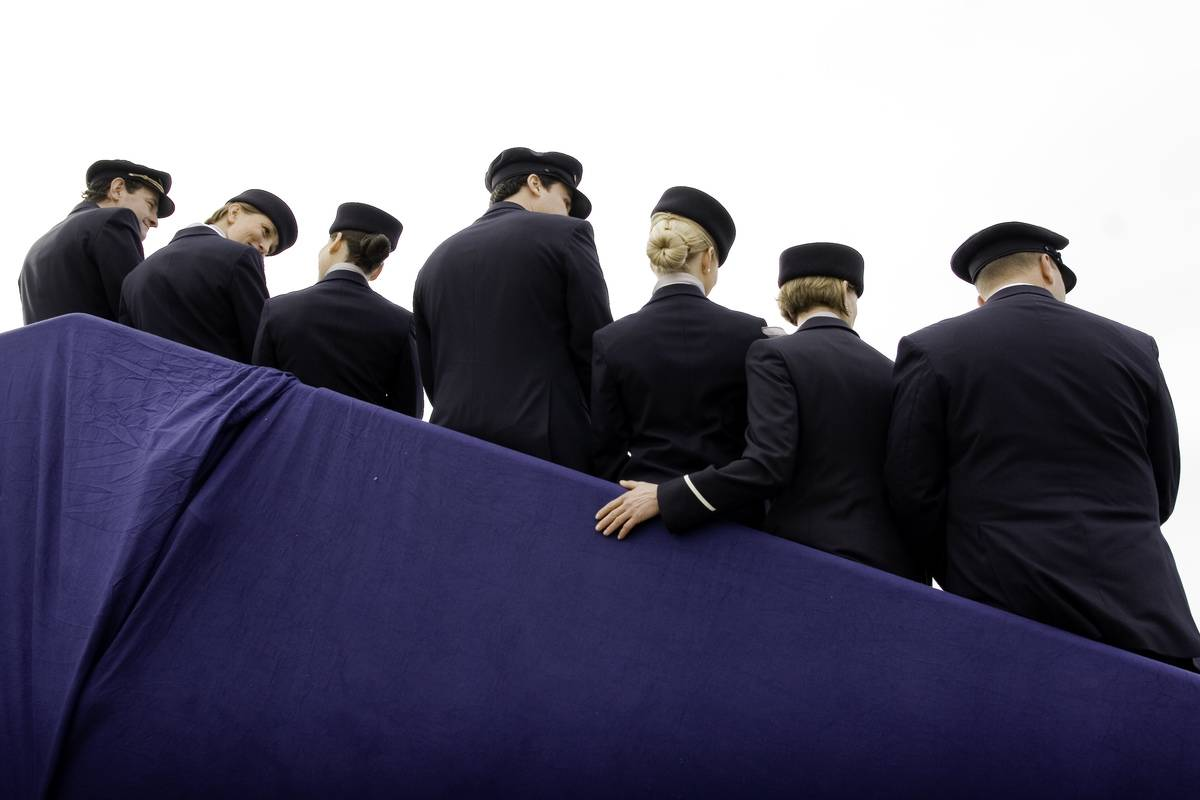 Flight attendants stand together on a staircase.
