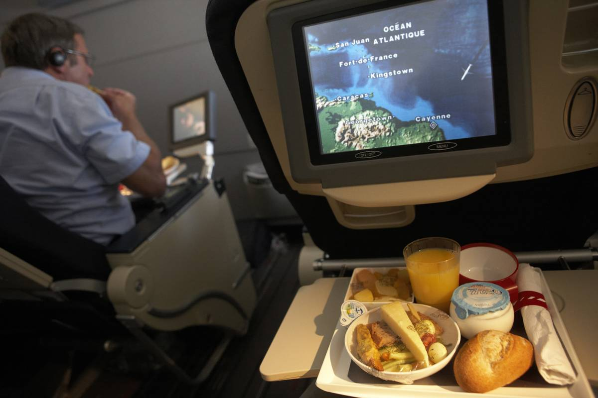 An on-board plane. meal sits on a tray below a TV screen.