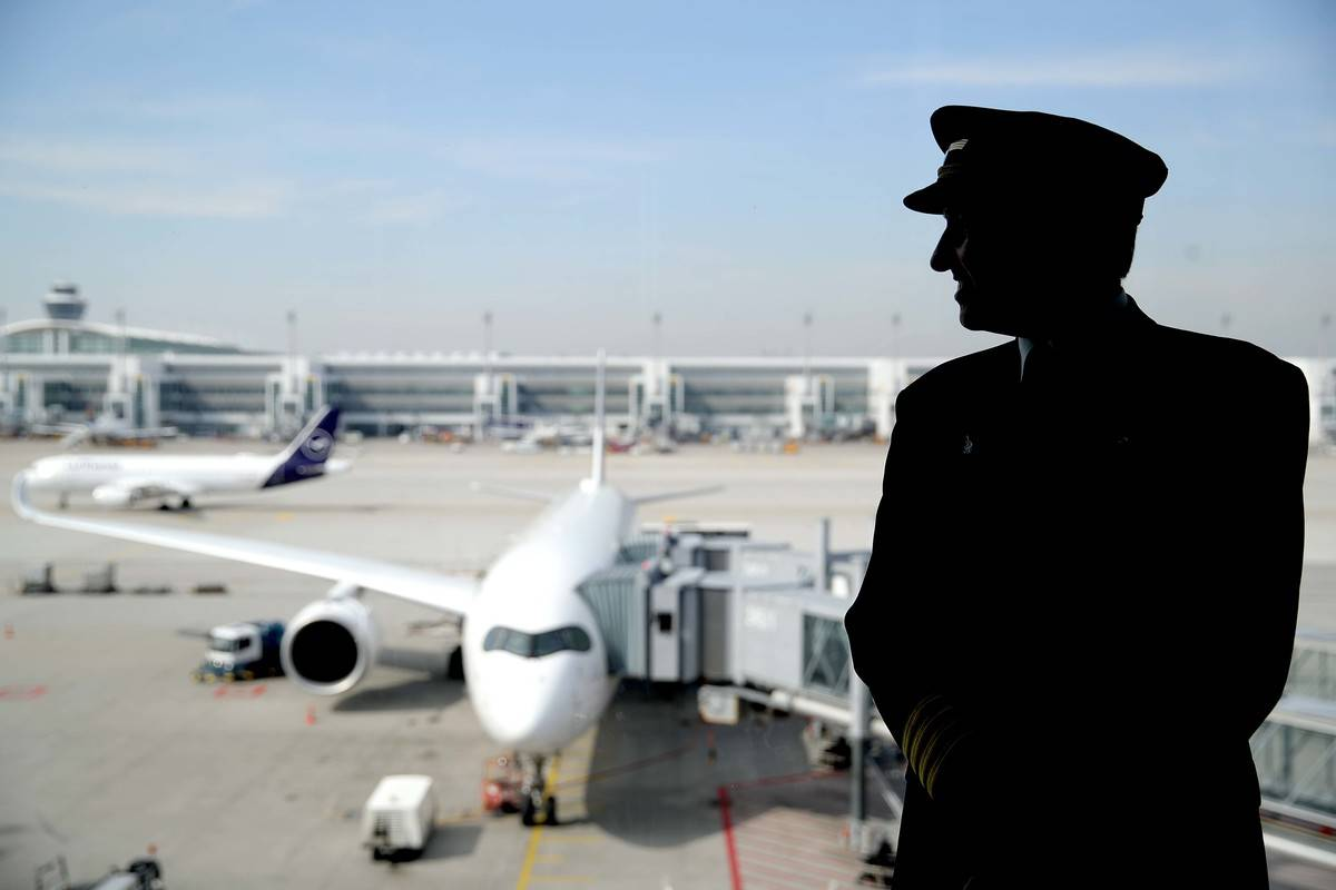 A silhouette of a pilot stands in front of a window with a plane in the background.