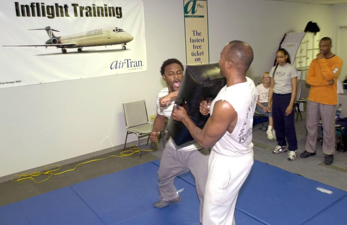 Two flight attendants practice self defense.