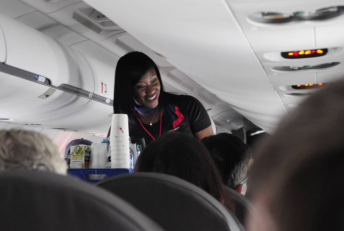 A flight attendant smiles as she serves drinks on a plane.