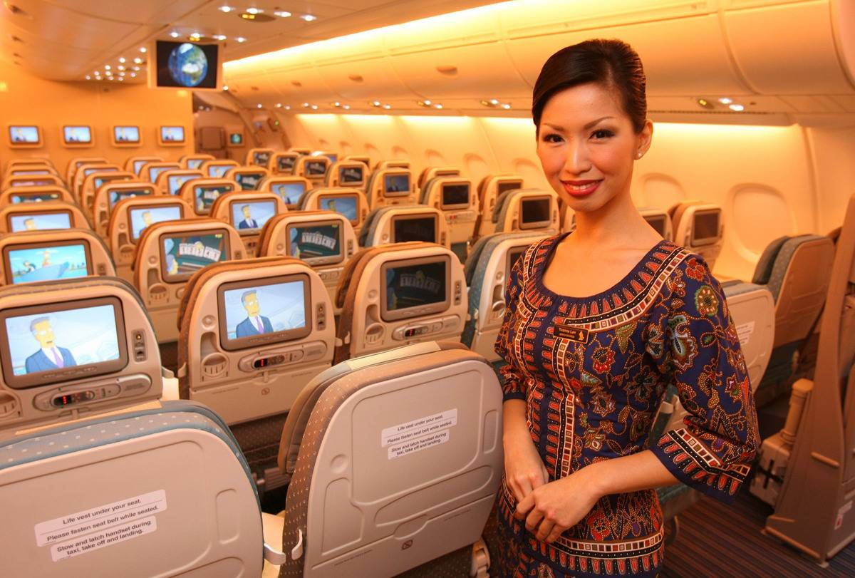 A stewardess from Singapore airlines smiles in an empty plane.