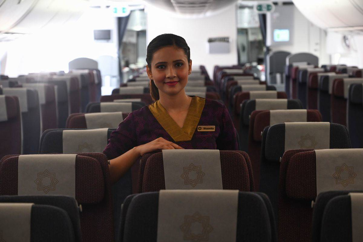 A stewardess smiles while standing amidst empty seats on a plane.