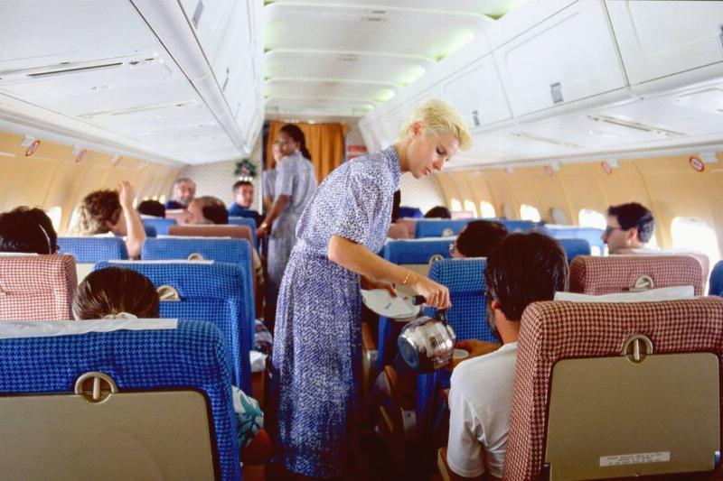 A stewardess serves a passenger in 1986.