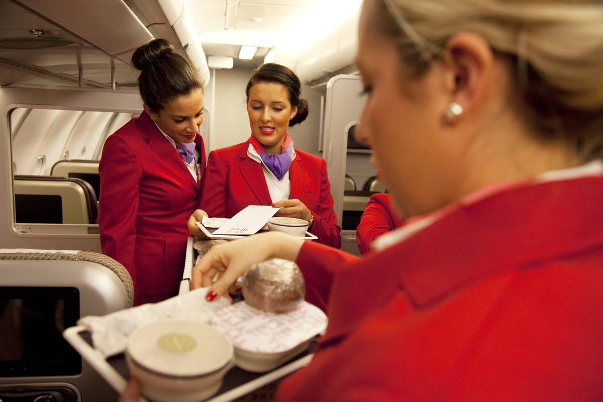 Three flight attendants talk together.