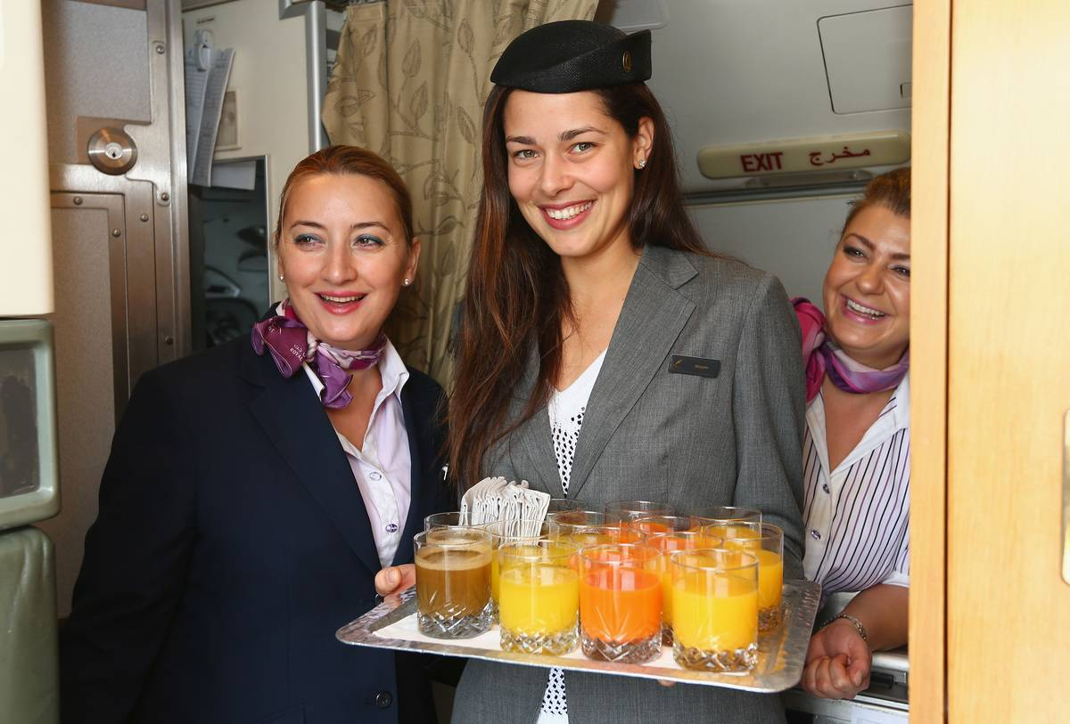 Flight attendants carry a tray of drinks to passengers.