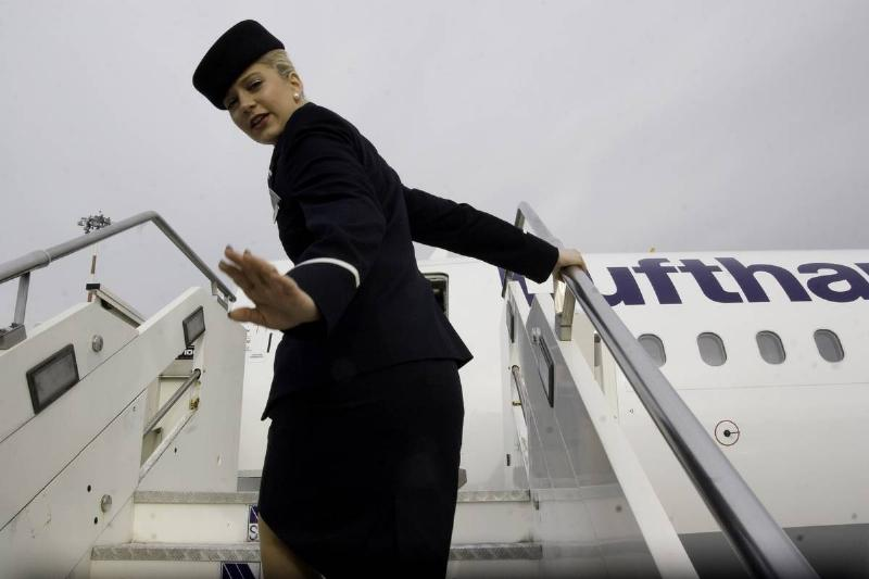 A flight attendant waves while boarding a plane.