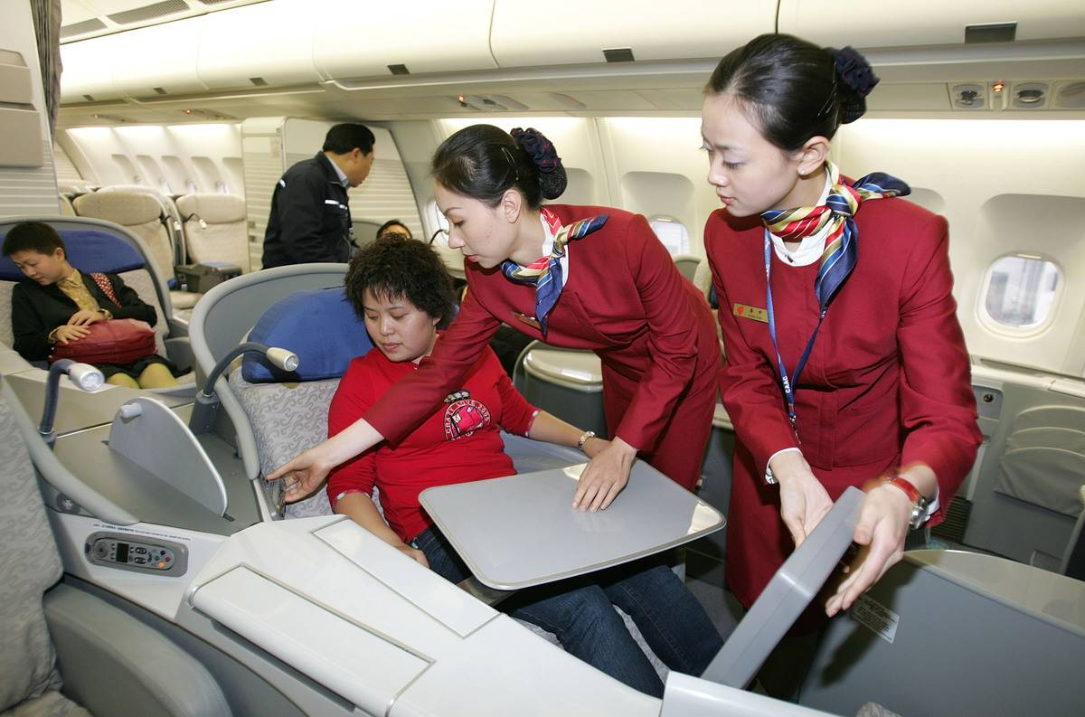 Two stewardesses help a child passenger together.