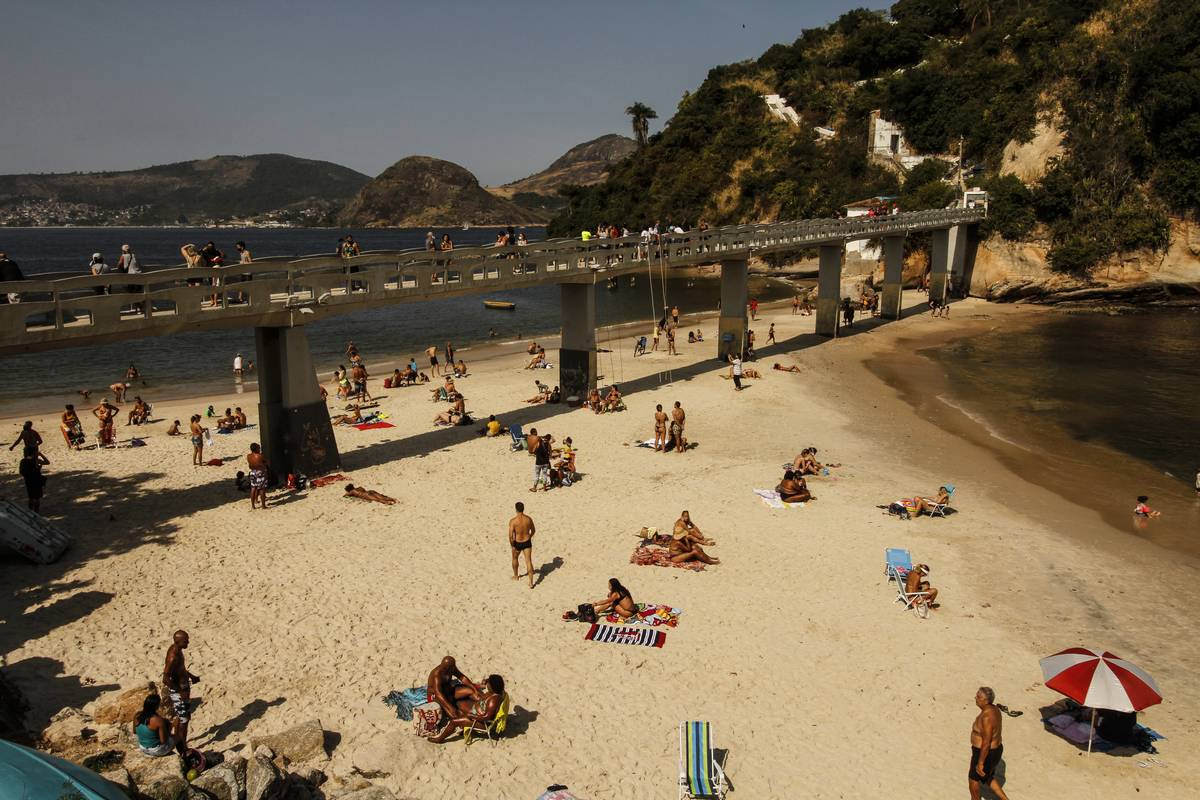 Beachgoers enjoy the weather underneath the bridge at Boa Viagem Beach, Brazil.