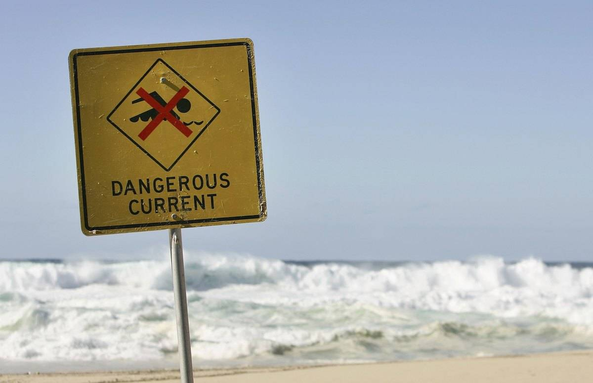 A sign warning about dangerous conditions is seen at Tamarama Beach.