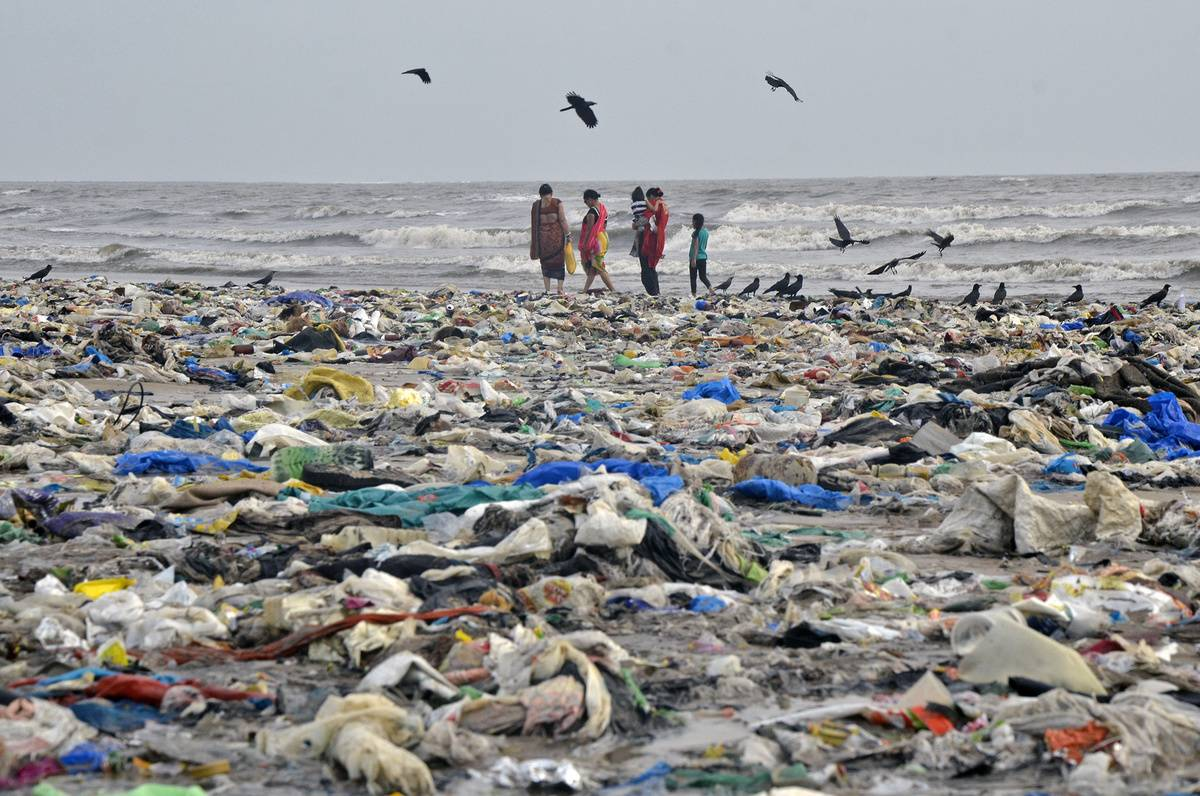 People walk across the trash-covered Juhu Beach in Mumbai, India.