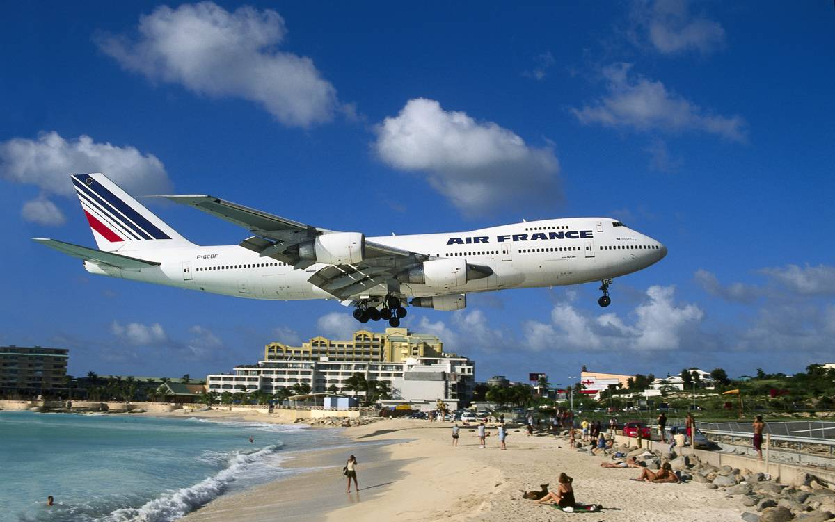 A French airliner flies directly above Maho Beach in the Caribbean.