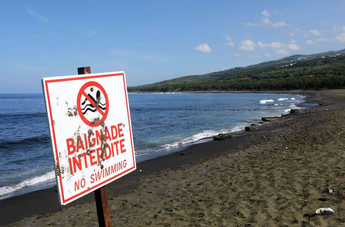 A sign dissuades visitors from swimming in the waters of Réunion Island, France.