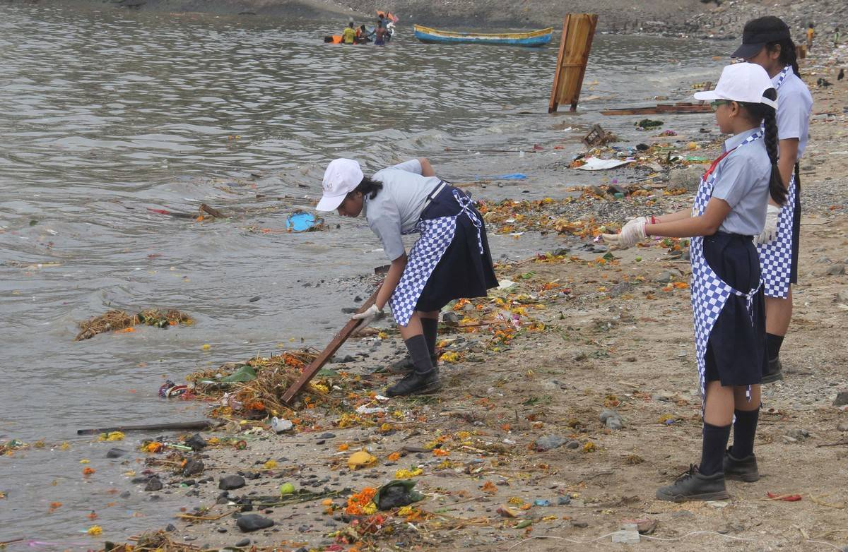Volunteers clean trash from Chowpatty beach, Mumbai.