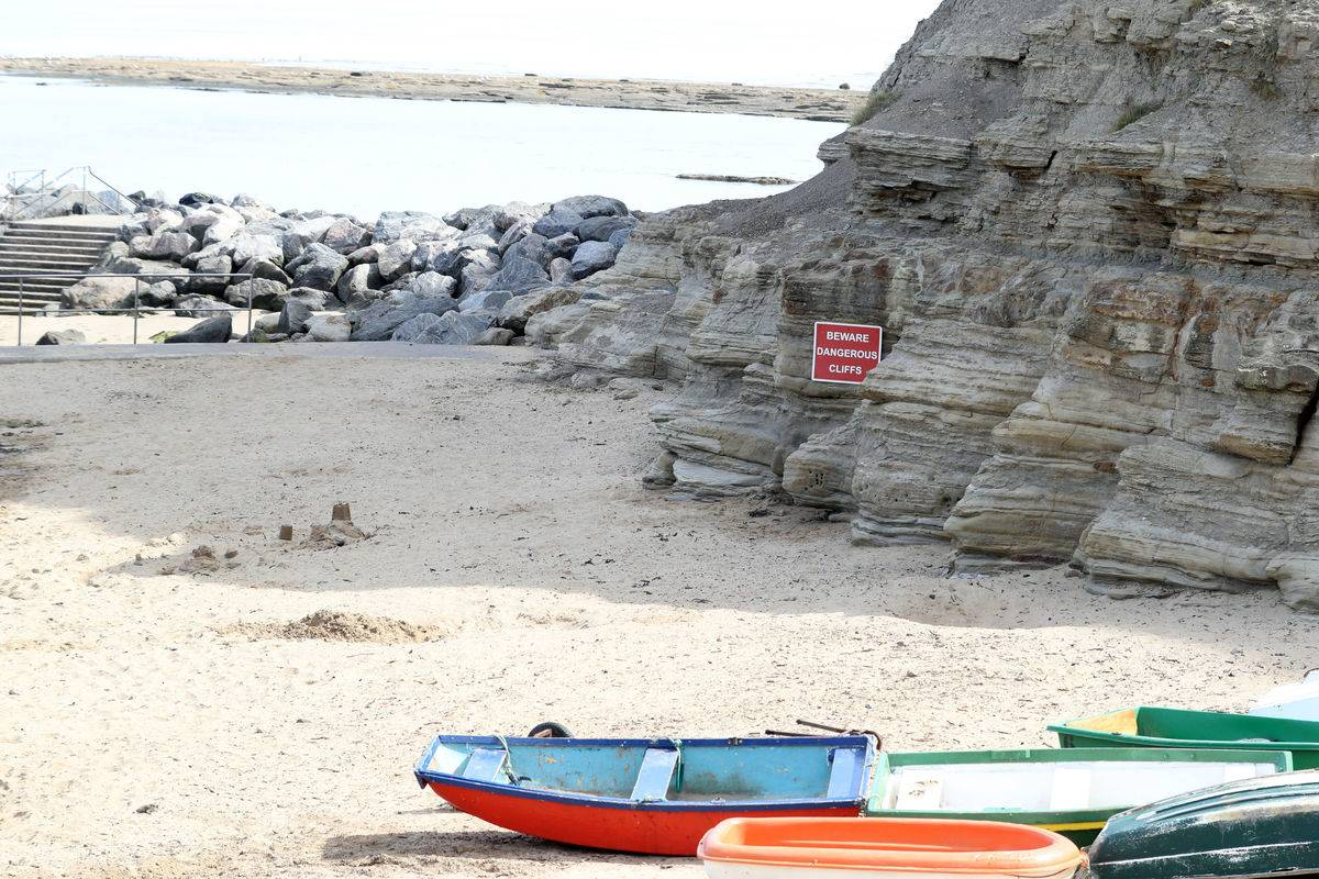 A sign on Staithes beach warns people about dangerous cliffs.