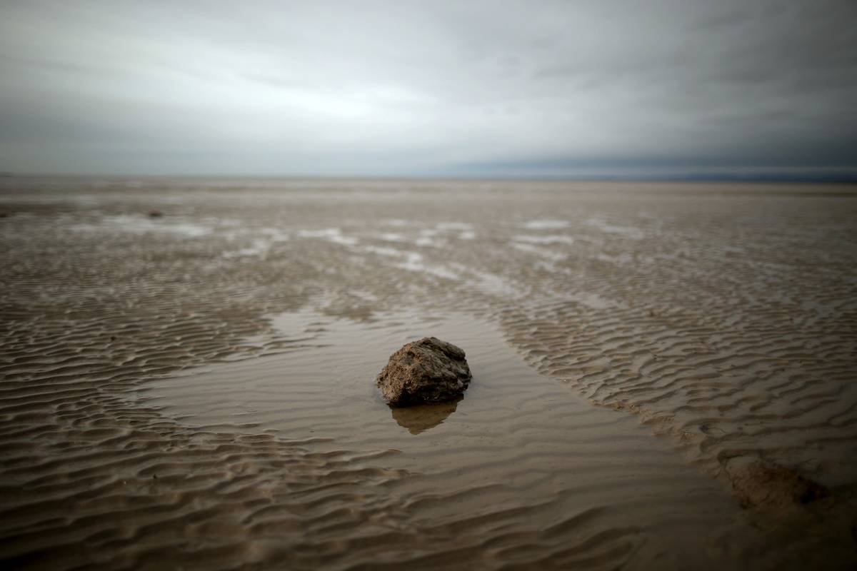 Quicksand is seen on the long shore of Morecambe Beach, England.