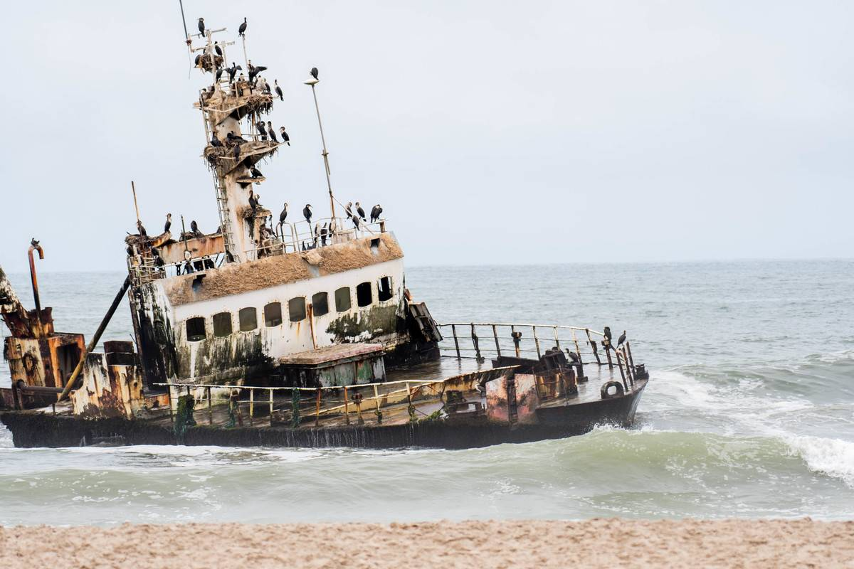 A shipwrecked ship appears on the coast of Skeleton Bay, Namibia.