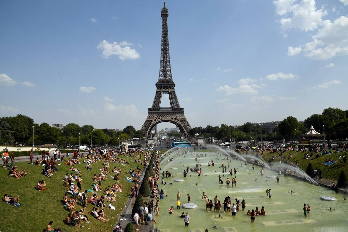 Crowds of people hang out in front of the Eiffel Tower, 2019.