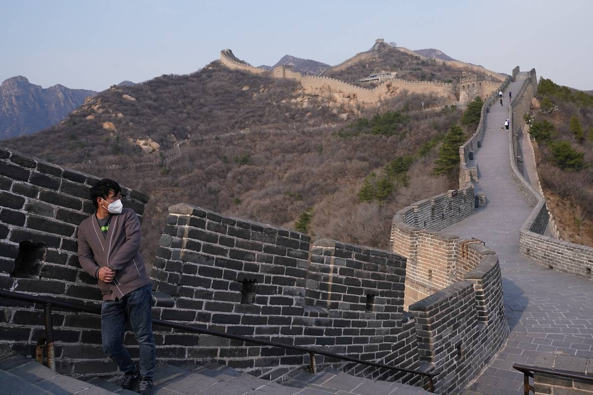 During the 2020 pandemic, a long visitor in a face mask leans against the Great Wall of China.
