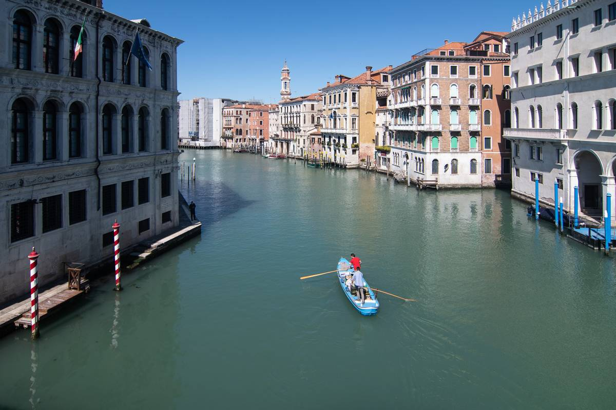 A long man on a boat sails through Venice canals in April 2020.