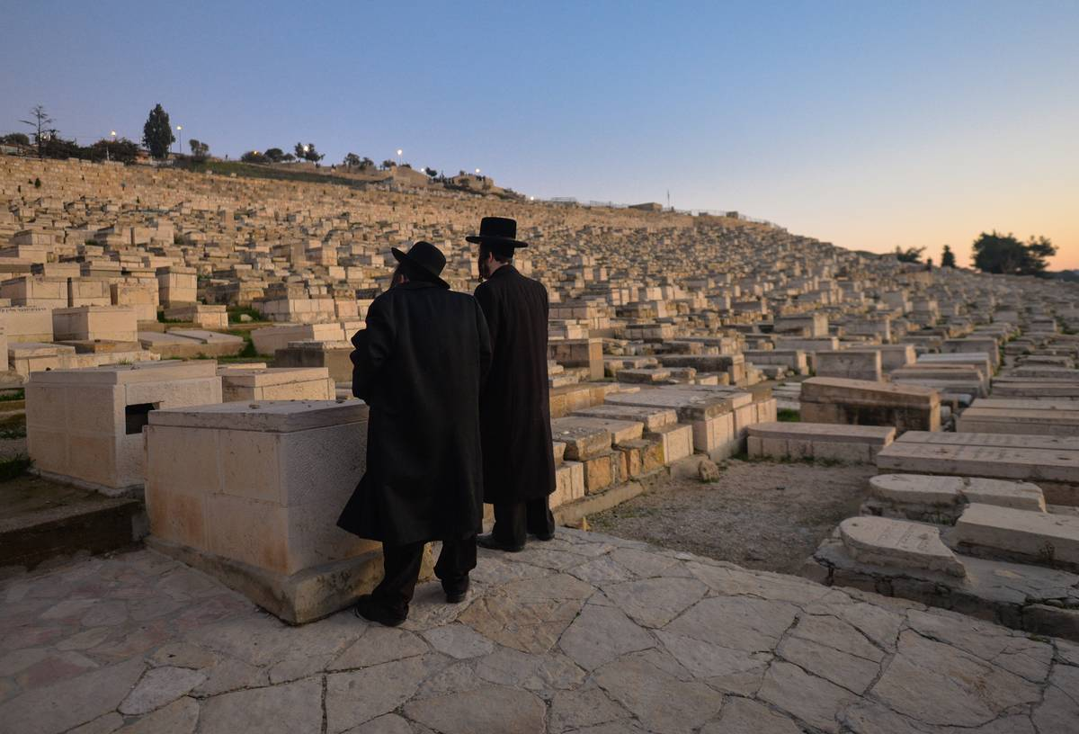 Visitors stand at the Mount of Olives Jewish cemetery.