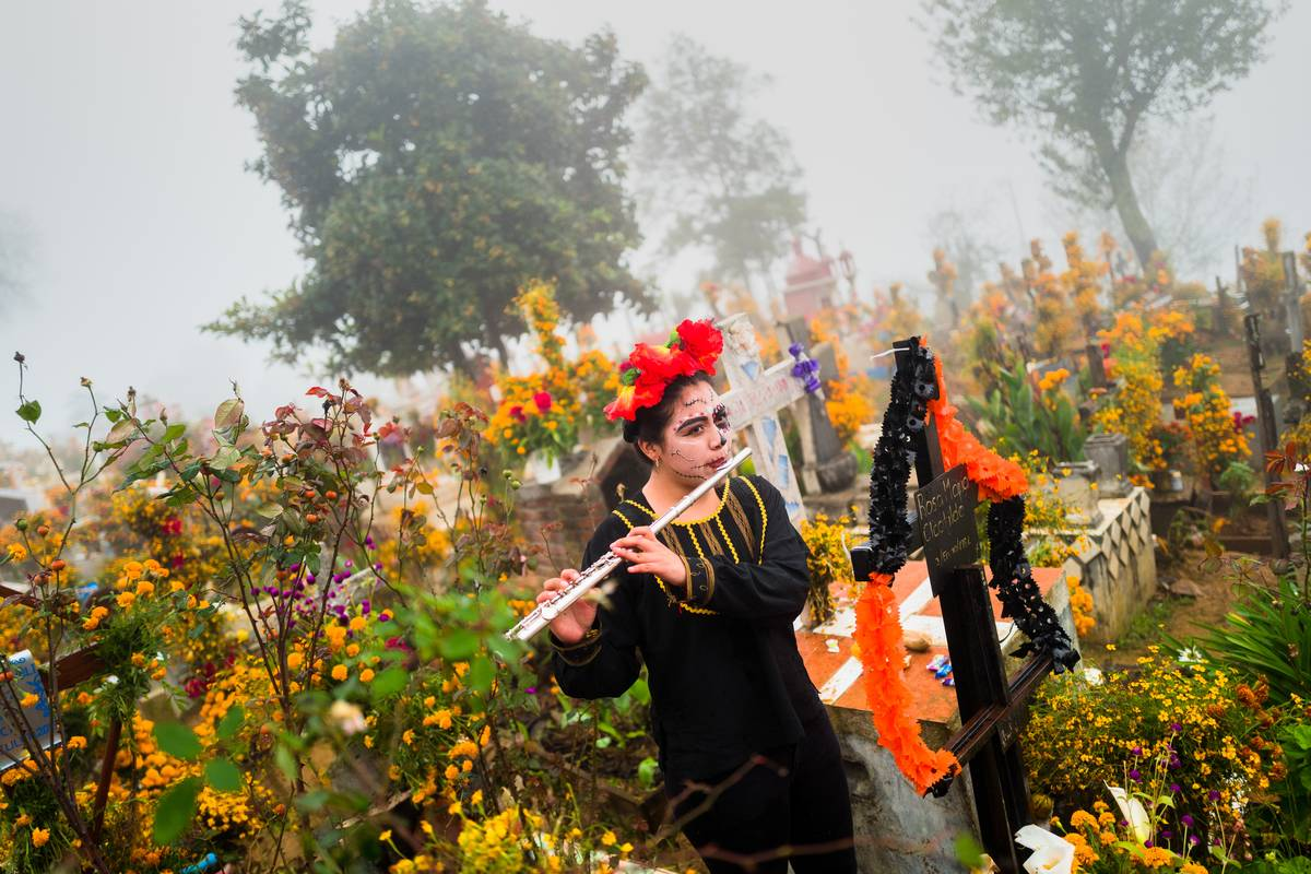 A woman plays the flute to celebrate the Day Of The Dead in Mexico.