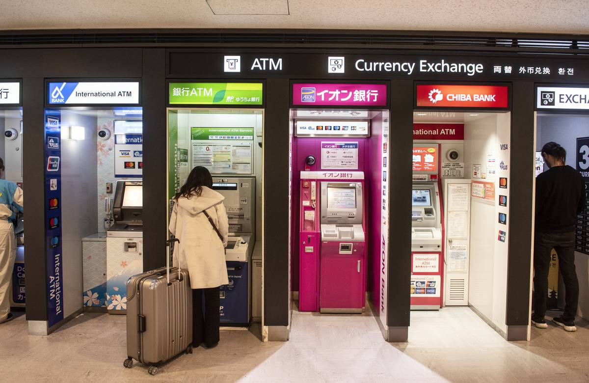 A woman gets cash at an airport ATM in Tokyo.