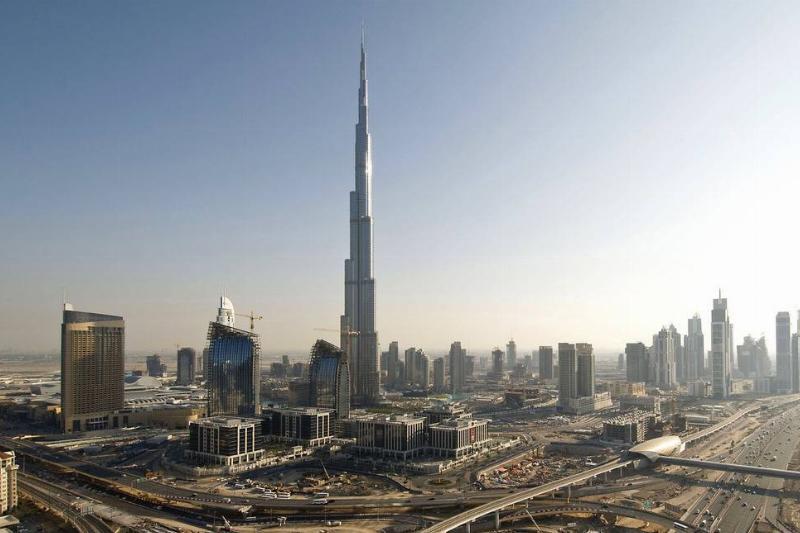 Burj Khalifa stands near freeways and other buildings in Dubai.