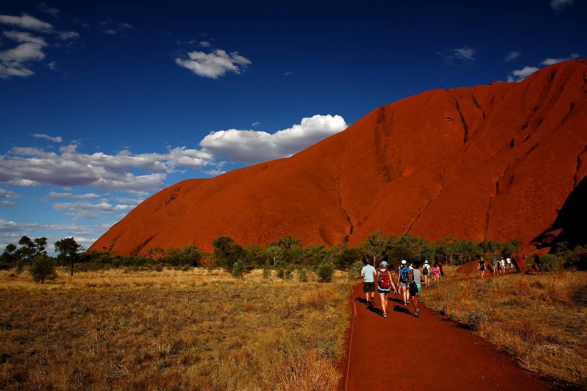 Hikers walk at the base of Uluru, the largest rock in the world.