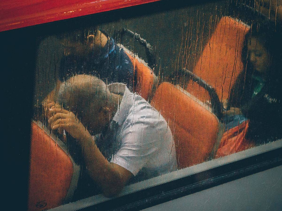 A man presses his head on the back of a bus seat as rain pours on the window.