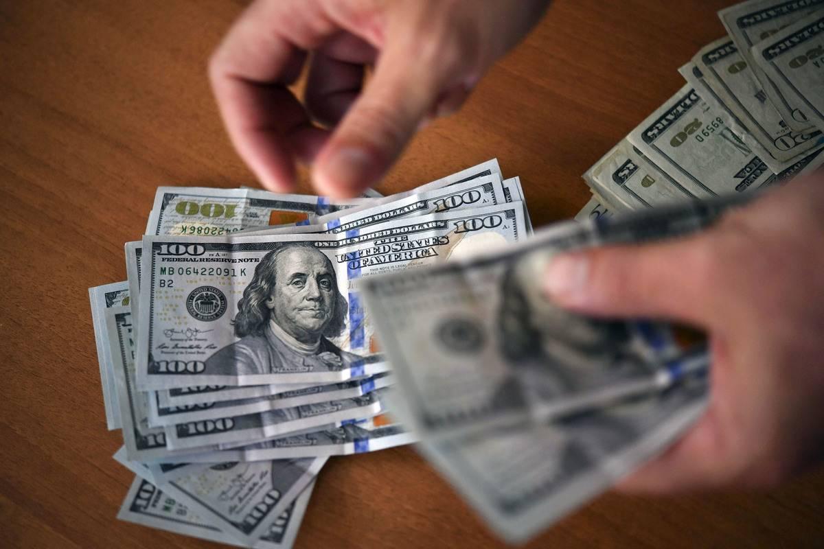 A person counts dozens of $100 bills.