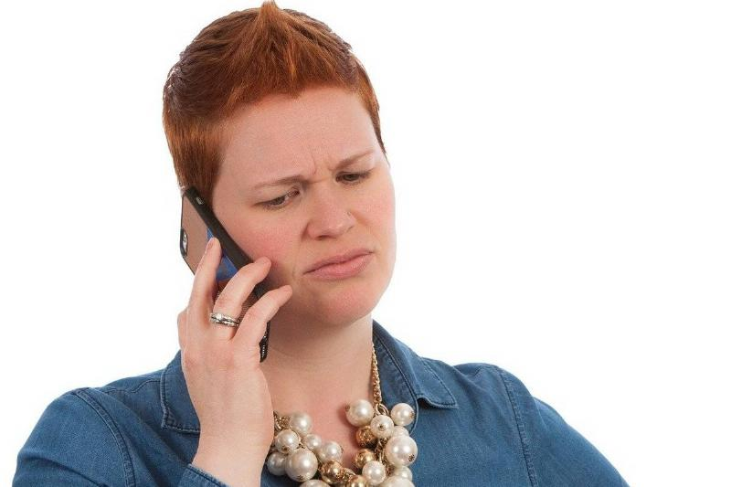 A woman looks upset on the phone.